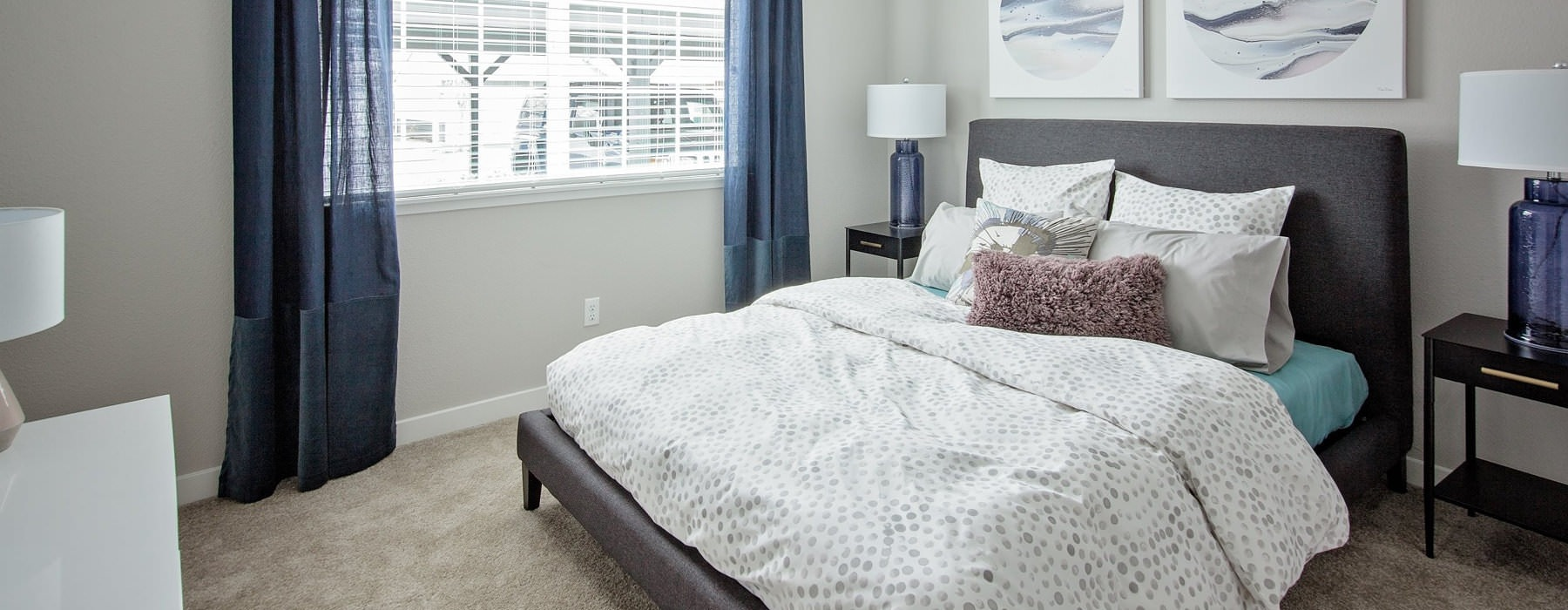 sizable bedroom with light fixture and wide windows